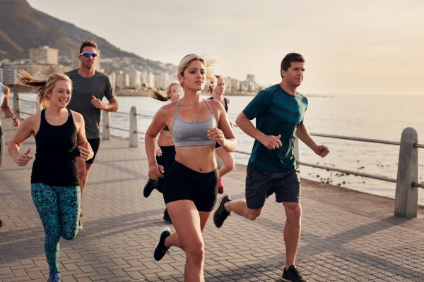 A group of runners running on pavement near the sea.